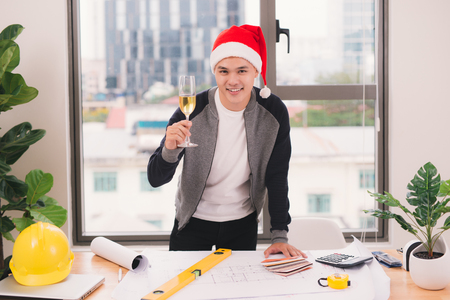 Male Asian architect celebrating the holidays at the office