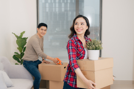 Loving couple enjoys a new apartment and keep the box in hands  Фото со стока