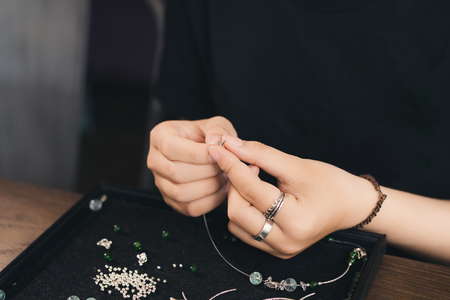 Female designer making jewelries at a jewelry shop Stock Photo