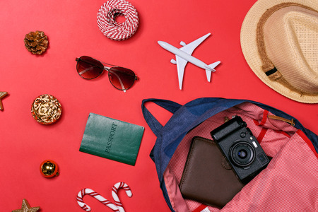 HOLIDAY travel concept - passport, camera, hat, airplane, chrismas decorations on red background