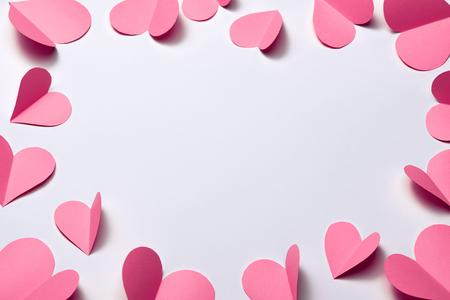 Beautiful pink paper hearts on white paper background Standard-Bild