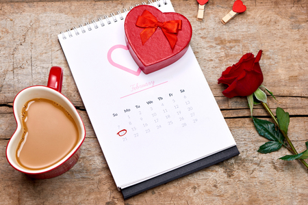 14th of February on calendar date . Red rose, hearts and gift box on wooden table. Valentine.
