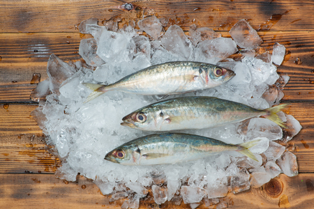 Fresh raw fish on ice on a wooden table. Stock Photo