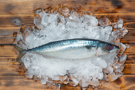 Fresh raw fish on ice on a wooden table. Stok Fotoğraf
