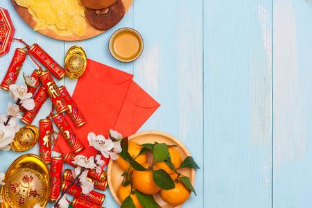 旧正月。爆竹と中国の金のインゴットと伝統的な赤の封筒と木製の背景に新鮮なオレンジと装飾 写真素材