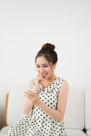 Young asian woman sitting on couch at home and using smartphone. Banque d'images