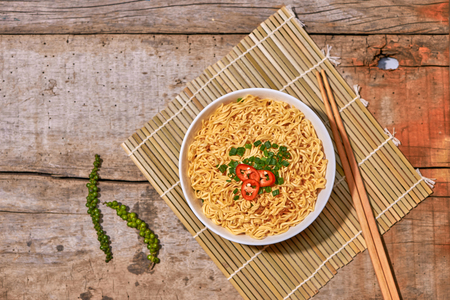 Instant noodle in bowl cooked spicy taste topping with eggs Imagens