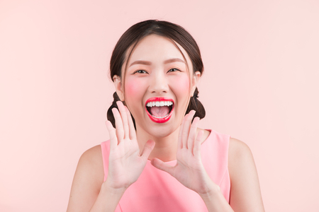Surprised young asian woman shouting over pink background Banco de Imagens