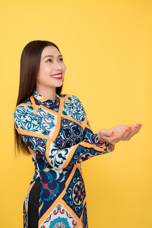 Vietnamese woman traditional festival costume Ao Dai gesture hands. Stock Photo