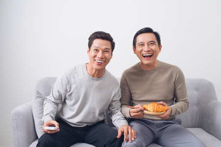 Twee mannelijke vrienden die op voetbalzitting op bank thuis letten Stockfoto