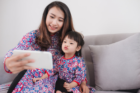 Vietnamese mother and daughter in Ao Dai Traditional dress, taking selfie photo.