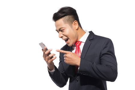 Angry businessman shouting on smartphone, standing over white background