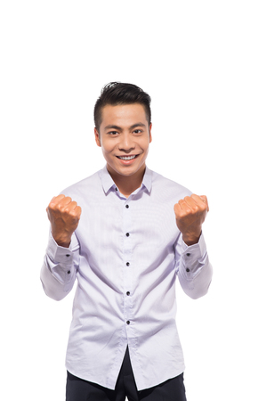 Portrait of an asian excited casual man standing with raised hands