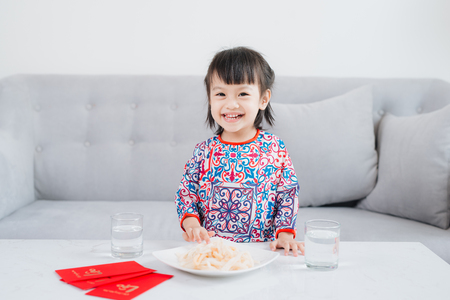 Vietnamese small girl in Ao Dai Traditional dress, celebrate new year at home. Tet Holiday.
