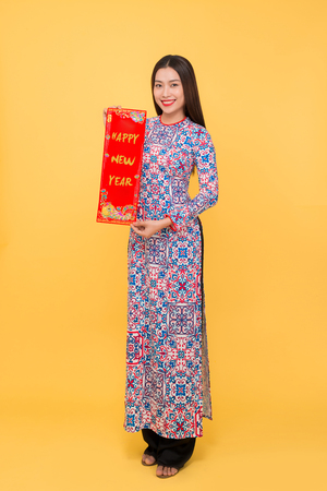 Full-length portrait of Vietnamese girl in ao-dai dress showing New Year scrolls