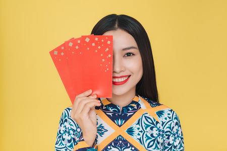 노란색 배경에 고립 된 전통 의상을 입고 매력적인 베트남 여자