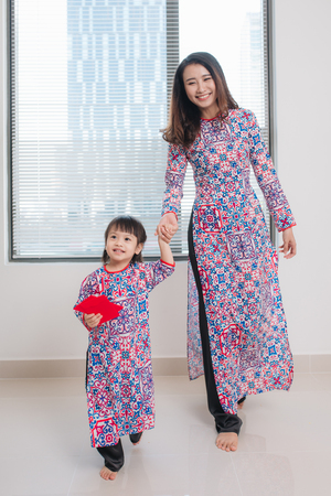 Vietnamese mother and daughter in Ao Dai Traditional dress, celebrate new year at home. Tet Holiday.