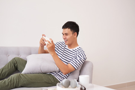 Young asian man sitting on sofa and playing games on phone at home