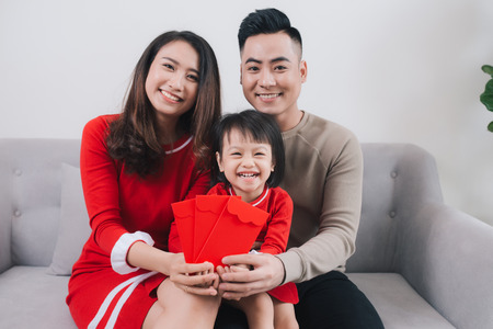 Happy Vietnamese family celebrate Lunar new year at home. Stock Photo