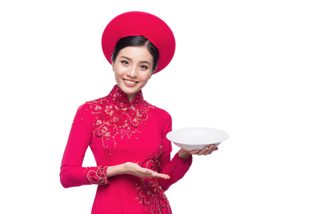 Smile Vietnamese woman in dress traditional Ao Dai and introduce product on white background. Stock Photo - 93168973