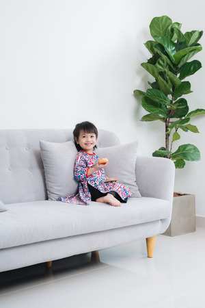 Beautiful little asian girl playing on the couch Stock Photo
