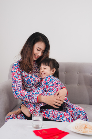 Vietnamese mother and daughter celebrate new year at home. Tet Holiday. Stock Photo