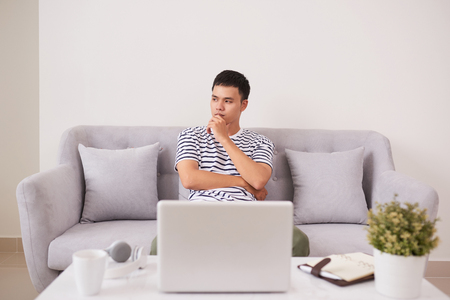 Young man looking up while working on laptop at home