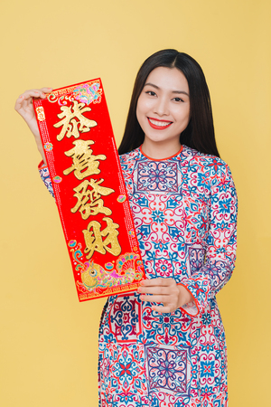 Attractive Vietnamese woman wearing traditional costume, isolated on yellow background. Text mean Happy New Year. Banco de Imagens
