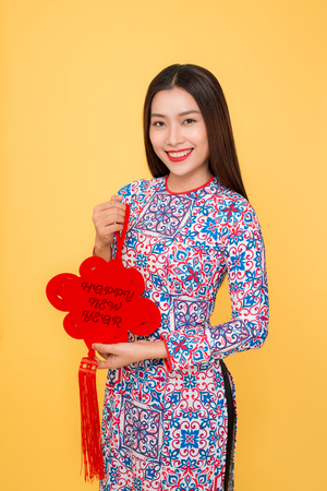 Vietnamese woman traditional festival costume Ao Dai holding attributes. Text mean Happiness.