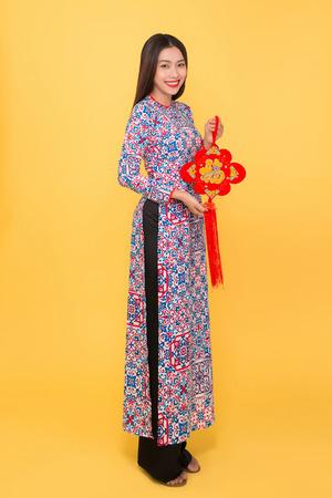 属性を保持するアオダイドレスのベトナムの女の子のフルレングスの肖像画。テキストは幸福を意味する