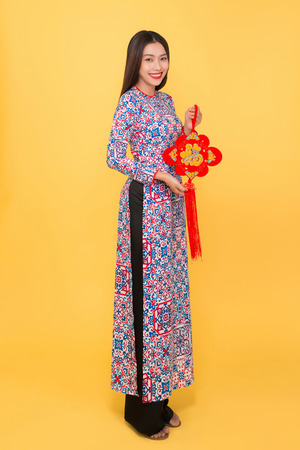 Full-length portrait of Vietnamese girl in ao-dai dress holding attributes. Text mean Happiness