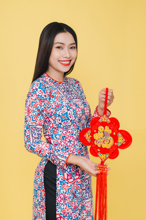 Attractive asian woman wearing traditional costume, isolated on yellow background. Text mean Happiness.