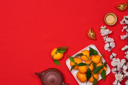 vier Chinees Nieuwjaar achtergrond met oranje fruit voor oorlogsschip, rode envelop en mooie bloesem. Stockfoto