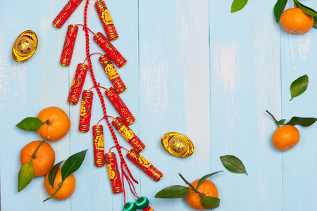 Lunar new year.Firecrackers and Chinese gold ingots and Traditional Red envelopes and decoration with Fresh oranges on wooden background Stock Photo