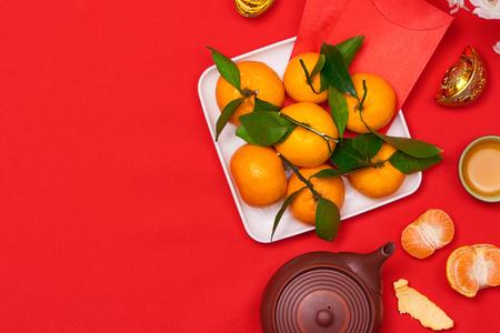 Bovenaanzicht accessoires Chinees Nieuwjaar festival decoraties. Oranje, blad, hout mand, rode pakket, op rode achtergrond. Stockfoto