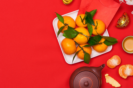 Top view accessories Chinese new year festival decorations.orange,leaf,wood basket,red packet, on red background.