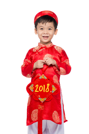 Cute little Vietnamese boy in red ao dai dress smiling. Tet Holiday. 2018