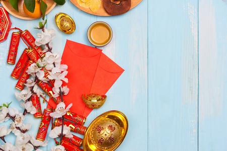 Voetzoekers en Chinese goudstaven en traditionele rode enveloppen en decoratie met verse sinaasappelen op houten achtergrond Stockfoto