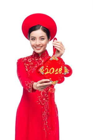Portrait of a beautiful Asian woman on traditional festival costume Ao Dai. Tet holiday. Lunar New Year. Text mean Happiness.