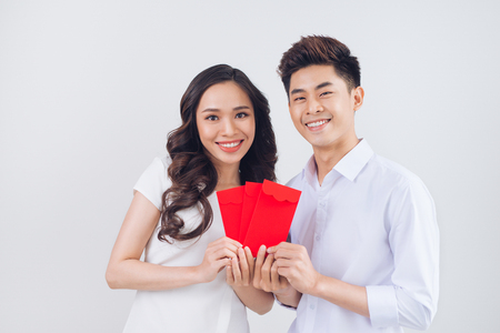Vietnamese couple exchanging red lucky money envelopes. Tet holiday. 스톡 콘텐츠