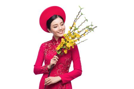 Portret van een mooie Aziatische vrouw op traditionele festivalkostuum Ao Dai die de boom van de Hoa Mai-boom (Ochna Integerrima) houden. Tet vakantie. Nieuw maanjaar.