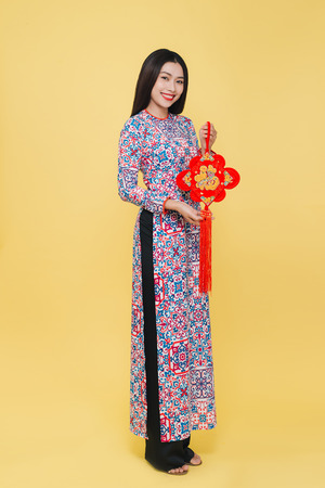 Attractive Vietnamese woman wearing traditional costume, isolated on yellow background. Text mean Happiness.