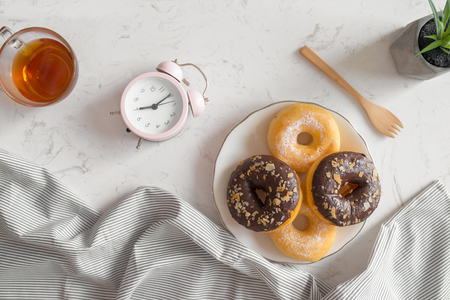 Top view of coffee cup with donut and clock on table. Standard-Bild
