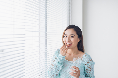 Young asian beauty young woman eating pills and drinking water  Stockfoto