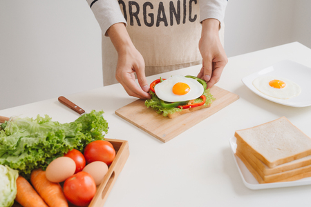 Preparing and eating breakfast at home in morning. Stock Photo