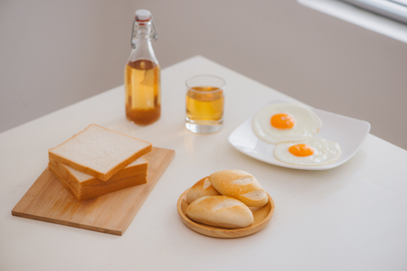 Morning breakfast with glass of tea, toast, fried eggs and bread on table