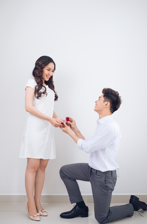 Happy beautiful Vietnamese girl looking at her boyfriend and smiling while getting a marriage proposal