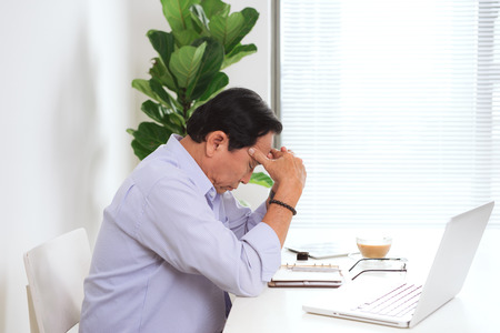 Senior man having headache with laptop and basic things for work at his desk