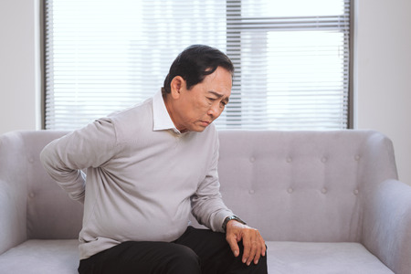 Senior asian man with pain in back sitting on sofa