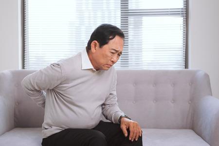 Uomo asiatico senior con dolore nella seduta posteriore sul sofà